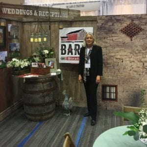 Barn Weddings Venue Manager Connie Hoffman awaits visitors at the opening of the Columbus Weddings Show in the Rustic Barn Wedding setting of the show booth.
